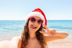 Young woman in on tropical beach. Young woman dressed in fashion swimsuit and santa hat using mobile phone camera for take se royalty free stock photos