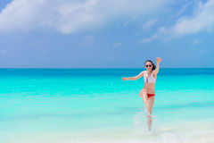 Young woman on a tropical beach splashing in shallow water Royalty Free Stock Photography