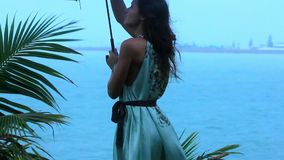 Young woman on a tropical beach with umbrella in. Rainy season. Video Koh Samui Thailand stock video footage