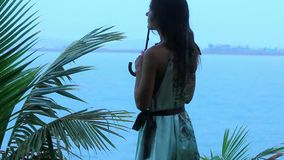 Young woman on a tropical beach with umbrella in. Rainy season. Video Koh Samui Thailand stock footage