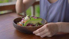 A young woman in a tropical cafe eat healthy vegetarian salad. Vegan food concept. Slowmotion shot
