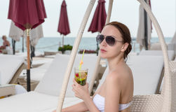 Young Woman with Tropical Drink on Resort Patio Stock Photos
