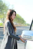 Young woman try to open the car door Stock Photos