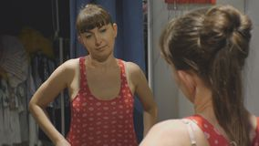 Young woman trying on clothes. Attractive caucasian female in a beige bra looks in the mirror putting on red shirt in. Clothing store`s fitting room stock footage