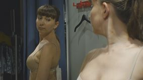 Young woman trying on clothes. Attractive caucasian female looks in the mirror turning around trying on beige bra in. Clothing store`s fitting room stock footage
