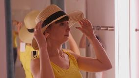 Young woman trying on clothes. Attractive caucasian female looks in the mirror turning her head trying on broad-brimmed. Straw hat in clothing store`s fitting stock video footage