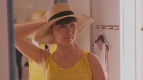 Young woman trying on clothes. Attractive caucasian female looks in the mirror turning her head trying on broad-brimmed. Straw hat in clothing store`s fitting stock video