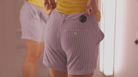 Young woman trying on clothes. Attractive caucasian female putting on striped blue shorts in clothing store`s fitting. Room. Thighs close-up stock video