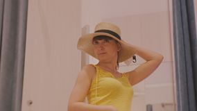Young woman trying on clothes. Attractive caucasian female tries on broad-brimmed straw hat holding by hand in clothing. Store`s fitting room stock video footage