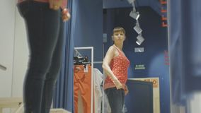Young woman trying on clothes. Low angle view of attractive caucasian female looking in the mirror spinning trying on. Red shirt and jeans in clothing store`s stock footage
