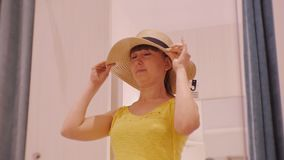 Young woman trying on clothes. Smiling caucasian female looks in the mirror turning her head trying on broad-brimmed. Straw hat in clothing store`s fitting room stock footage