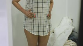 Young woman trying on clothes. Tilt view of attractive caucasian female looking in the mirror trying on blouse in. Clothing store`s fitting room stock video