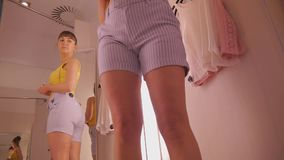 Young woman trying on clothes. Tilt view of attractive caucasian female looking in the mirror at her hips turning around. Trying on blouse in clothing store`s stock footage