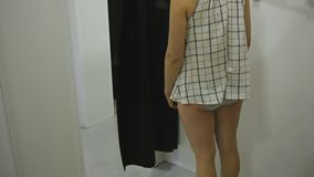 Young woman trying on clothes. Tilt view of attractive caucasian female looking in the mirror turning around trying on. Blouse in clothing store`s fitting room stock video footage