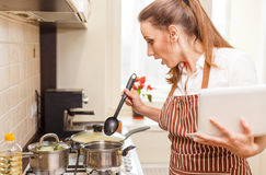 Young woman trying cooking with recipe from laptop Royalty Free Stock Photo