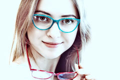 Young woman trying on different pairs of eyeglasses Stock Photography
