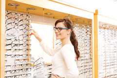 Young woman trying on glasses. Young woman checking out options for glasses Royalty Free Stock Photography