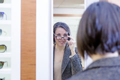 Young woman trying on glasses Royalty Free Stock Image