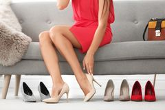 Young woman trying on high-heeled shoes Stock Photo