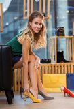 Young woman trying high heeled shoes at store royalty free stock photography