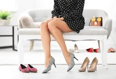 Young woman trying on high-heeled shoes Royalty Free Stock Image