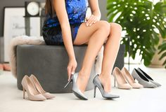 Young woman trying on high-heeled shoes. In store royalty free stock photo
