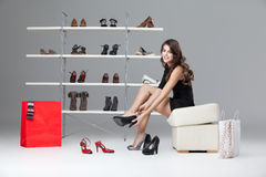 Young woman trying on high heels. Young woman trying on black high heels Royalty Free Stock Images