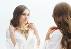 Young woman trying new jewelry in a studio Stock Image