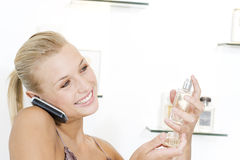 Young woman trying perfume at the beauty counter and talking on her mobile phone Royalty Free Stock Images