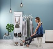 Young woman trying on shoes. Stylish dressing room interior stock photography