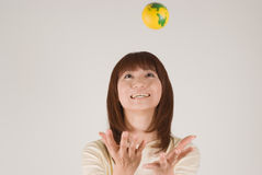 Young woman trying to catch a ball. Young Asian woman trying to catch an earth ball Royalty Free Stock Photos