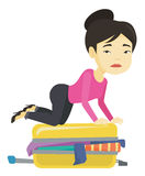 Young woman trying to close suitcase. Asian woman sitting on suitcase and trying to close it. Sad woman having problems with packing a lot of clothes into a Royalty Free Stock Images
