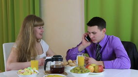 Young woman trying to communicate with her husband at breakfast. He pays no attention to it. Business man talking on. A smartphone stock footage