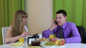 Young woman trying to communicate with her husband at breakfast. He pays no attention to it. Business man talking on stock video footage