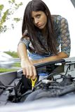 Young woman trying to fix engine of broken car Royalty Free Stock Image