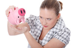 Young woman trying to get money from her piggy Stock Images