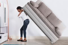 Woman Trying To Move Large Sofa Stock Image
