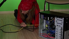 Young woman trying to repair computer under table. Static shot. 4K UHD stock footage