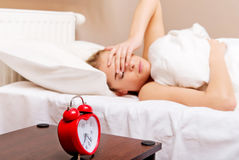 Young woman trying to sleep when alarm clock ringing Stock Photo