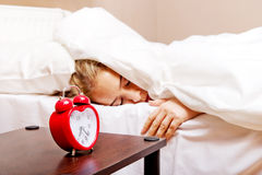 Young woman trying to sleep when alarm clock ringing Royalty Free Stock Photography