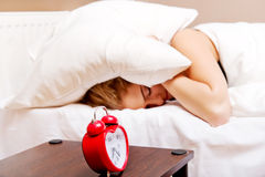 Young woman trying to sleep when alarm clock ringing Royalty Free Stock Image