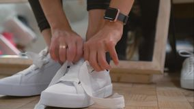 Young woman trying on white sneakers in a store.  stock footage