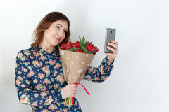 Young woman with tulip bouquet  and cell phone. Young woman with pink tulip bouquet and cell phone. 8 march, international womens day, mothers holiday. Spring Stock Photos