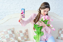 Young woman with tulips taking photo of herself Royalty Free Stock Photos