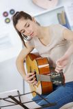 Young woman tuning guitar Royalty Free Stock Images