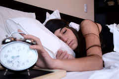 Young woman turning off alarm clock Royalty Free Stock Photography
