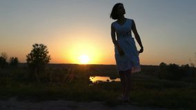 Young Woman Turns The Hem of Her White Folk Dress at Nice Sunset stock video footage