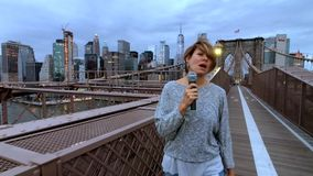 Young woman TV reporter is broadcasting walking on Brooklyn bridge