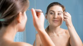 Portrait of young woman with tweezers at mirror. Young woman with tweezers at mirror in bathroom stock photo
