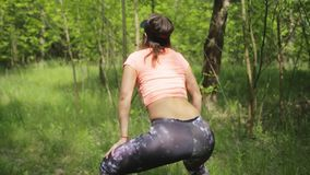 Young woman twerking. Outdoors in spring green forest stock footage